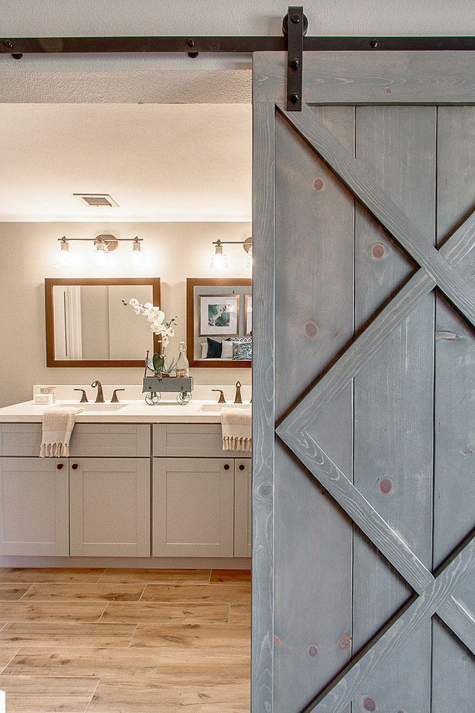 Blissful Abode Interiors - Bathroom with gray vanity, white quartz, wood tile floor, sliding barn door #whitebathrooms #vanity