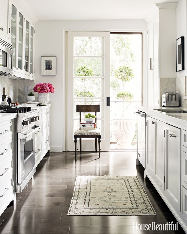 The traditional white kitchen features custom-made cabinets painted in Farrow & Ball's All White.