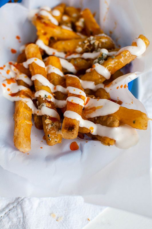 Buffalo Fries are topped with cheese and drizzled with buffalo sauce and ranch. Game day perfection.