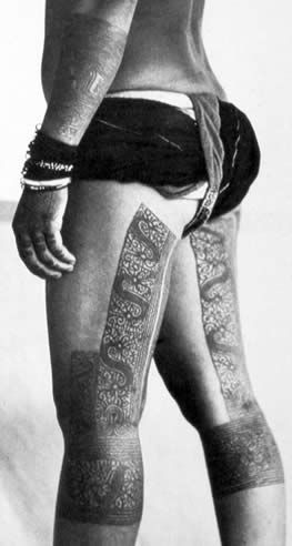 Snake-like aso' (dragon-dog) tattoos slither down this Kayan woman's legs, ca. 1925. They combined with other tattoo forms to repel evil and to induce fertility.