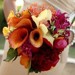 mango callas, yellow cymbidium orchids, pincushion protea, burgundy dahlias, coral hypericum and gloriosa lilies