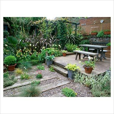 Small jungly urban garden - Sandstone terrace with granite table and benches, railway sleepers and gravel with Thrift and grasses, Phormium tenax 'Atropurpureum', Trachycarpus fortunei, ferns, Stipa gigantea, Cordyline, Tulipa, wallflowers, Hostas and Buxus sempervirens in pots, Pergola covered in climbers