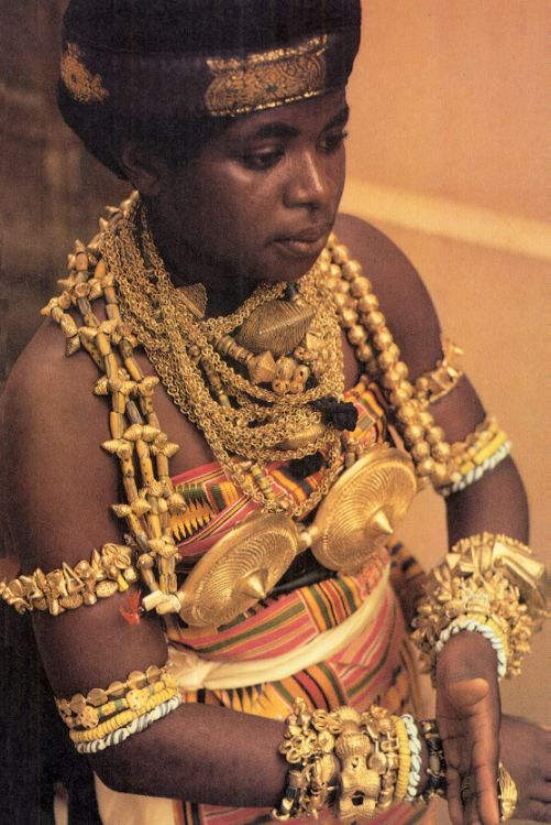 Africa | Ashante ~ Adosawa dancer is adorned with many gold bracelets, gold and glass beads (mixture of Venetian glass beads from the African trade period and more simple ones made locally by the Krobo)are attached on cotton threats to the neck, arms and waist.  The final item to be placed is the large gold breast-shaped ornament | Caption and image © Angela Fisher, African Adorned