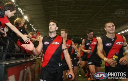Jobe Watson high fives a young fan after Essendon won the AFL Round 01 match between the North Melbourne Kangaroos and the Essendon Bombers at Etihad Stadium, Melbourne. (Photo: Andrew