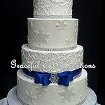 Elegant Winter Wonderland White Butter Cream Wedding Cake with Sugar Crystals, Snow Flakes, Royal Blue Ribbon and Bling by Graceful Cake Creations