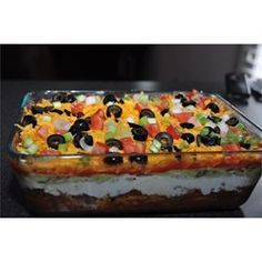 My mom's Seven Layer Dip is a big hit at all small gatherings! Refried beans are layered with guacamole, seasoned sour cream, veggies and cheese. It's perfect for dipping tortilla chips! The dip traditionally takes less time to disappear into bellies than it does to prepare.