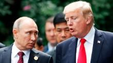 """US President Donald Trump (R) and Russia's President Vladimir Putin talk as they make their way to take the """"family photo"""" during the Asia-Pacific Economic Cooperation (APEC) leaders' summit in the central Vietnamese city of Danang on November 11, 2017. World leaders and senior business figures are gathering in the Vietnamese city of Danang this week for the annual 21-member APEC summit. / AFP PHOTO / POOL / JORGE SILVA (Photo credit should read JORGE SILVA/AFP/Getty ..."""