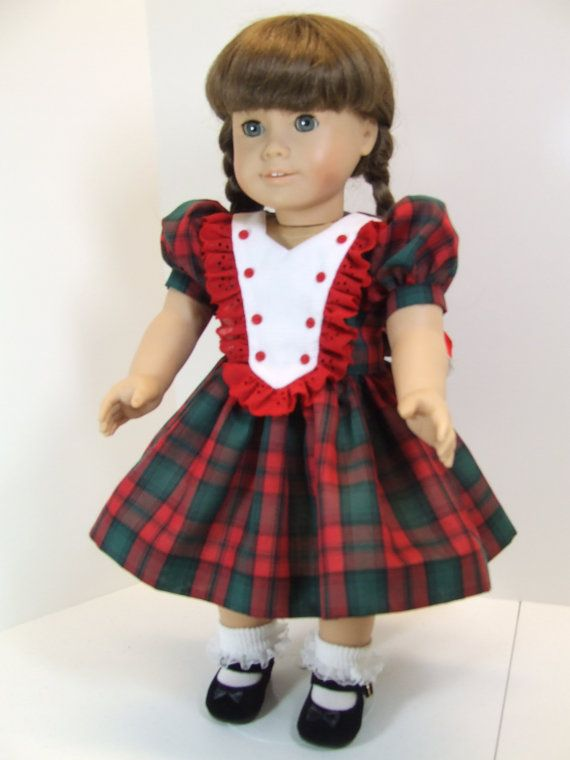 My doll is modeling a dress thats perfect for Christmas, since its a dark red and hunter green plaid cotton. The bodice is lined in white, and the full gathered skirt has an attached white slip. The bodice front has a white pique bib front, edged in matching red eyelet lace, and trimmed with tiny red buttons.  The plaid puffed sleeves are cut on the bias, and the dress ties in back at the waist in a bow. The back closure is done with working buttonholes and buttons.  Please feel free to ask…