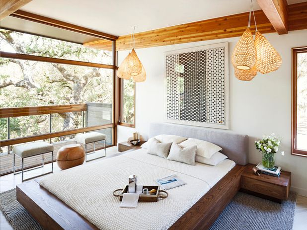 Beautiful, rustic bedroom design with exposed wooden beams, framed graphic print, white bedding, floor to ceiling windows and a wooden bed frame with a suede headboard | MAS Design
