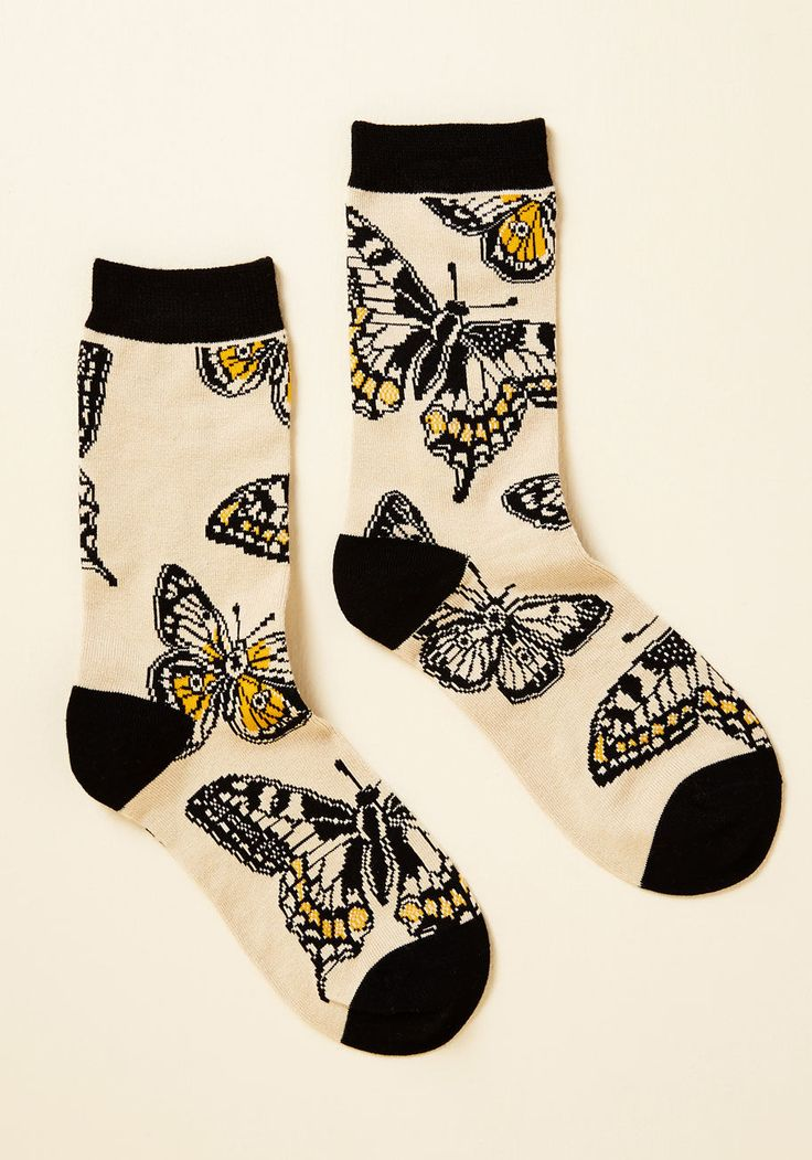 <p>Jupiter nor Mars will have nothing on Earth when your toes grace the ground with these beige crew socks in tow! Patterned with black and marigold mariposas, this knit pair will let you 'wing' among the stars!</p>