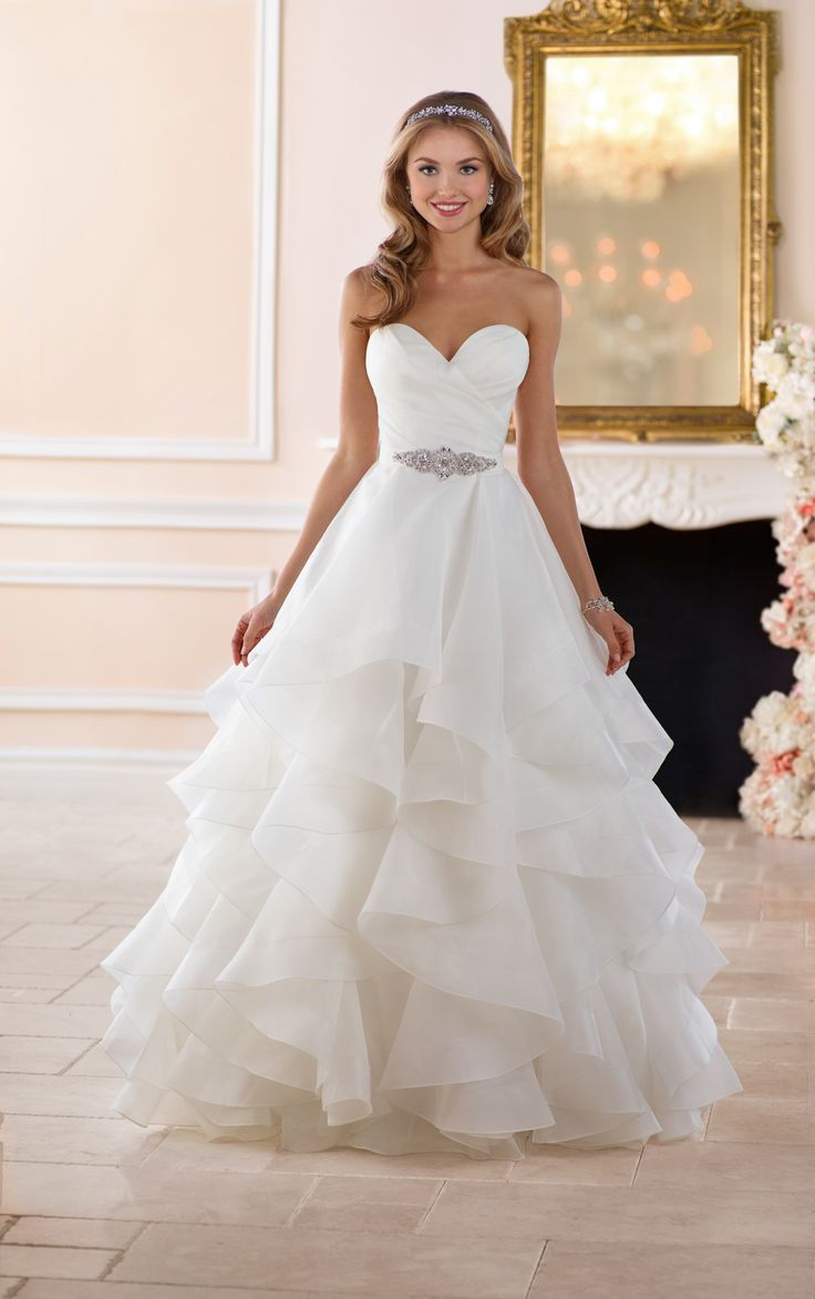 This dramatic layered skirt wedding dress from Stella York is truly a sight to behold. This classic ball gown made of Royal organza has a voluminous skirt with multiple layers that looks full but feels light and airy. The ruched organza bodice in a classic sweetheart neckline gives a sense of timelessness while the skirt is modern and fresh. Fabric covered buttons over an easy-close zipper finished the back for a comfortable fit. This dramatic wedding gown is available in plus sizes.