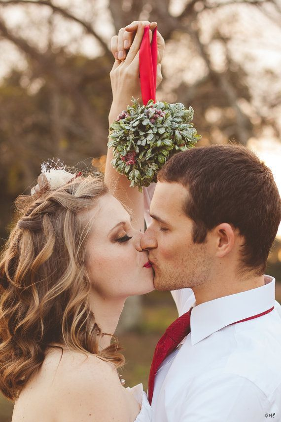 A photo of you kissing under the mistletoe at your winter wedding. Oh my heart!