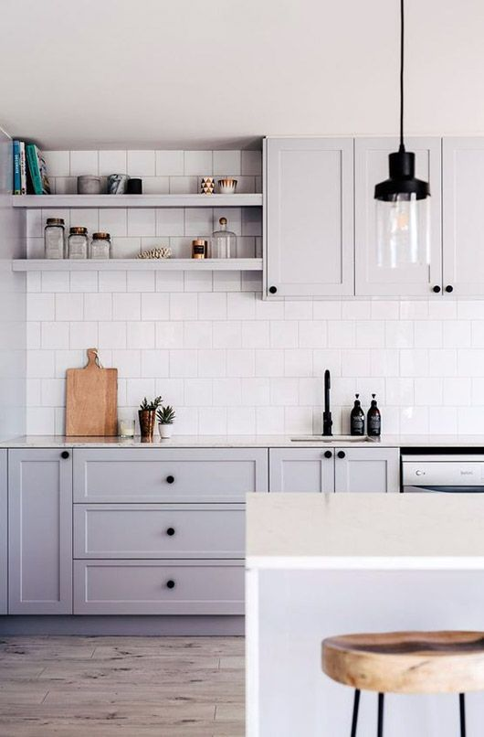 gray kitchen cabinets with white tile backsplash and black pendant lights. / sfgirlbybay