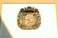 Znak města Jaroměře: Městský znak Jaroměře, lev uvnitř trnové koruny, je umístěn nad průchodem zvonicí při kostele sv. Mikuláše na její východní straně. Nese letopočet 1707.