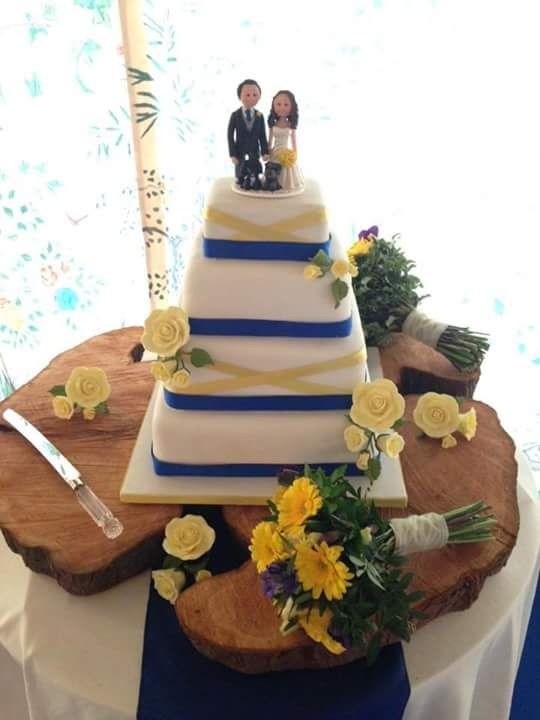 Lovely yellow cake flowers to match perfectly with the little yellow bouquet the cake- topper bride is holding! A very sweet contemporary square wedding cake.