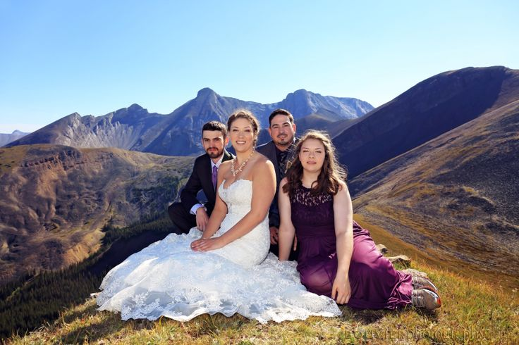 Wedding party sitting on top of mountain for group pose. Mountain top wedding. Summer heli-wedding. Canmore Alberta wedding.