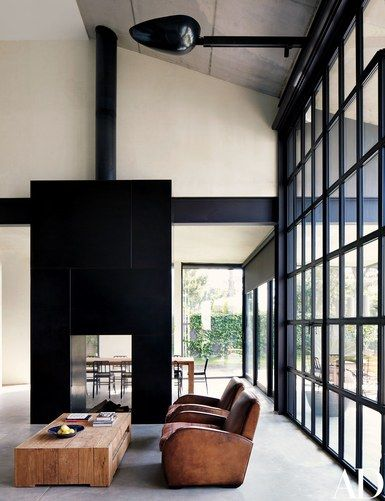 In the living room, leather club chairs by Harvey Brown and a custom-made cocktail table by Heerenhuis are grouped before a double-sided hearth clad in blackened steel | archdigest.com