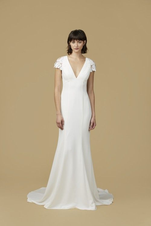 V-neck crepe gown with hand appliqued floral cap sleeves and open back from Nouvelle Amsale. Available in Ivory.