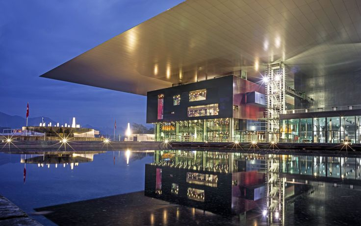KKL Lucerne, a multiuse cultural building and convention center in Switzerland, sits on the bank of Lake Lucerne and appears to extend over the water. Two water channels divide the structure into three parts, which are connected by the roof.