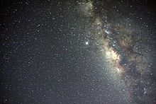 The Galactic Center is the rotational center of the Milky Way. The estimates for its location range from 7.6 to 8.7 kiloparsecs (about 25,000 to 28,000 lightyears) from Earth in the direction of the constellations Sagittarius, Ophiuchus, and Scorpius where the Milky Way appears brightest. There is strong evidence consistent with the existence of a supermassive black hole at the Galactic Center of the Milky Way