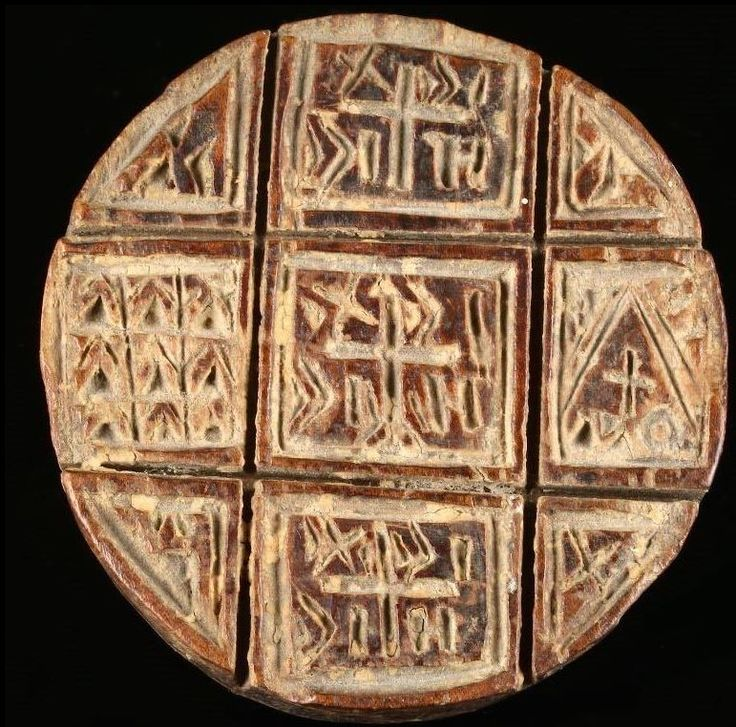 """Coptic bread stamp of wood, 4th-7th century A.D. Prosphora stamp, these stamps are used for bread intended for consecration and communion within the various ancient Christian traditions. The inscription is IC XC NI KI, which stands for """"Jesus Christ, Victor"""" Stamp carved into nine sectors, each decorated with different geometric motifs, including crosses and triangles, the rectangular handle carved at the top with another cross and abstract motif, 8.5 cm diameter. Private collection"""