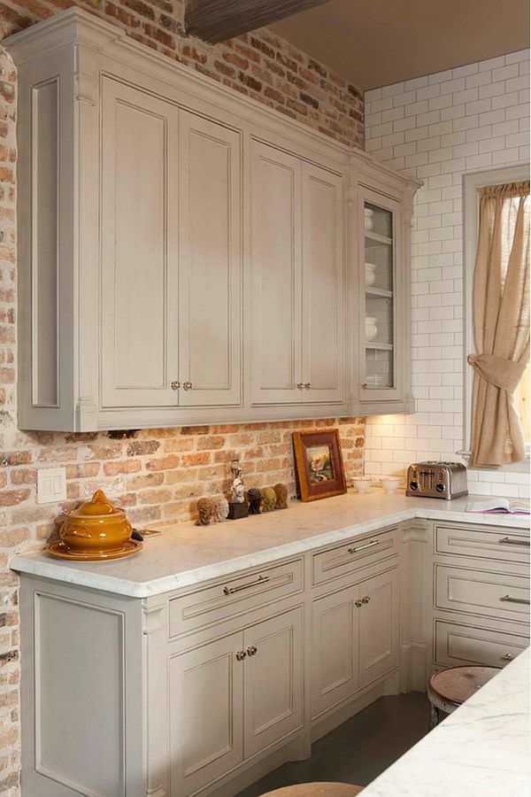Gray Kitchen Cabinet against Brick Backsplash and White Honed Carrara Countertop