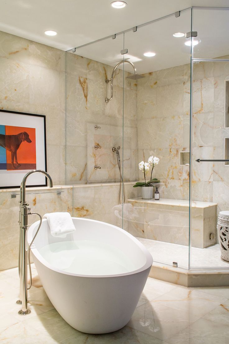 Master Bathroom with white onyx tiles covering floors and walls.  Frameless glass shower enclosure, Porcelanosa Freestanding Almond Tub, Waterworks fittings