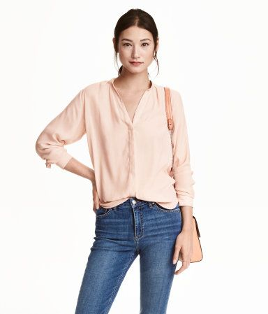 Powder pink. Long-sleeved blouse in airy woven fabric. V-neck, concealed buttons at front, pearlescent buttons at cuffs, and rounded hem. Slightly longer at