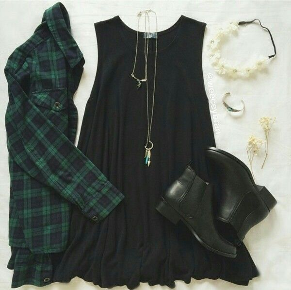 short black sleeveless sun dress, black and dark green plaid collared button up shirt, black ankle boots, and long necklace.