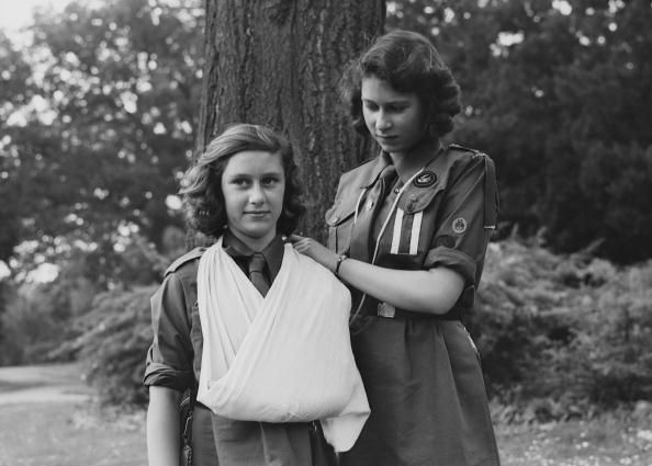 Princess Elizabeth places Princess Margaret's arm in a sling as part of the girl guides in Frogmore, Windsor, England on April 11, 1942.
