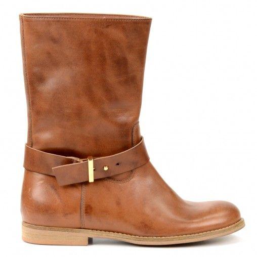 Simpele korte laarzen in cognac. De laarzen zijn gemaakt van dun leer, waardoor ze merkbaar soepel en licht lopen. Om de schacht zit een bandje met gouden gesp dat van de laars afgehaald kan worden zodat er een simpele laars overblijft. De laarzen zijn ge