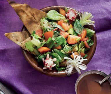 Fattoush, en syrlig sallad som du serverar med rostade pitabröd, knaprigt och fräscht. Salladen består bland annat av gurka, tomat, rädisor och olika lökar medan syrligheten kommer från den citronbaserade dressingen med sumak.