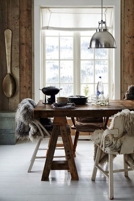 White painted floorboards, reclaimed wood walls, and layers of sheepskins.