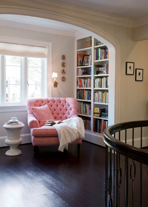 This bright pink comfy reading chair brings some cheer to this small book nook. The natural light from the windows and the full floor-to-ceiling bookshelves complete the scene.