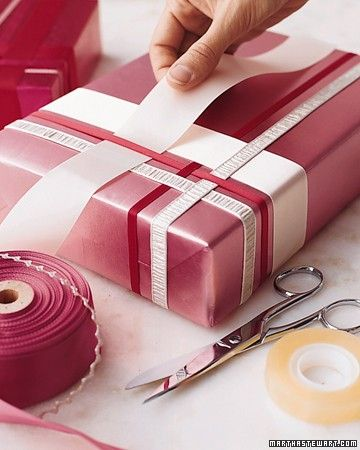 Here's our idea of thinking outside the box: interweaving ribbons to dress up a gift. The weaving begins with a single ribbon stretched across the top of the package, its loose ends fixed to the bottom with double-sided tape.