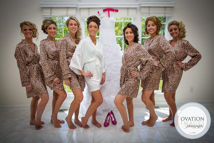 bride posing with her bridesmaids before the wedding. They are all wearing leopard print robes