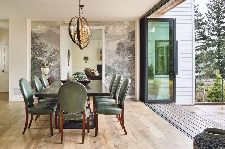 "A new 16-foot-long folding glass wall in the dining area ""turns this whole room into an outdoor deck,"" homeowner Anne Tucker says. The gold-and-black ""killer chandelier"" is by Crystorama; the table and chairs are Ralph Lauren.  (Benjamin Benschneider/The Seattle Times)"
