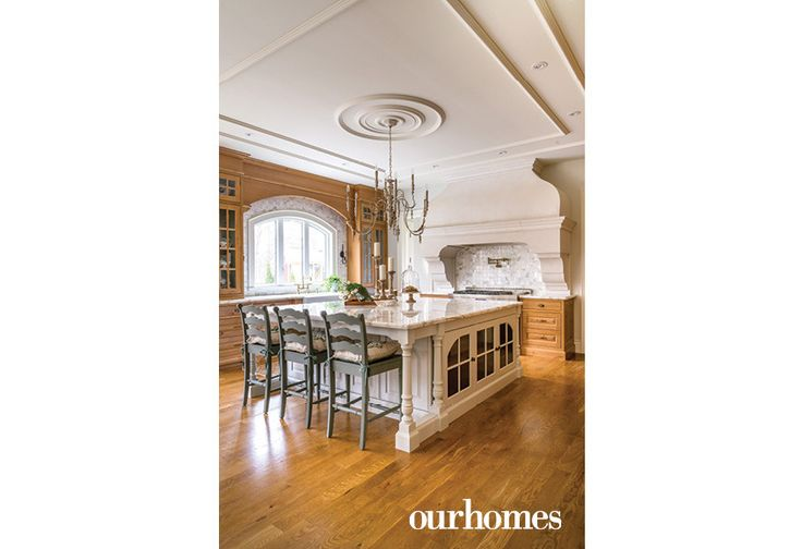"In line with a classic English country feel, the homeowners designed an oversize precast stone range hood and chose Calacatta Gold marble countertops.    See more of this home in ""Alder Cabinetry with Visible Knots Bucks the White Trend"" from OUR HOMES York Region, Summer 2017 http://www.ourhomes.ca/articles/build/article/alder-cabinetry-with-visible-knots-bucks-the-white-trend"