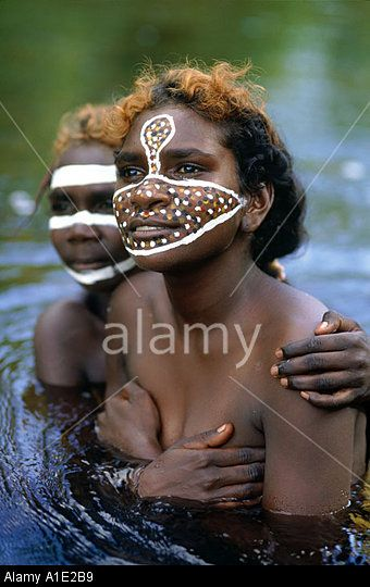 Sisters Tessa and Jane painted with their traditional totems in a billabong near Ramingining Arnhem land NT Australia