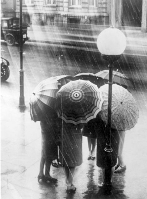 General Photographic Agency - A group of women stand underneath umbrellas in the London rain. 1928. S)