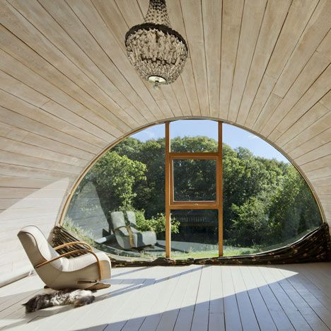 The vaulted ceiling design of this small house addition creates an intimate space for its user that elegantly frames a view to the outside world.