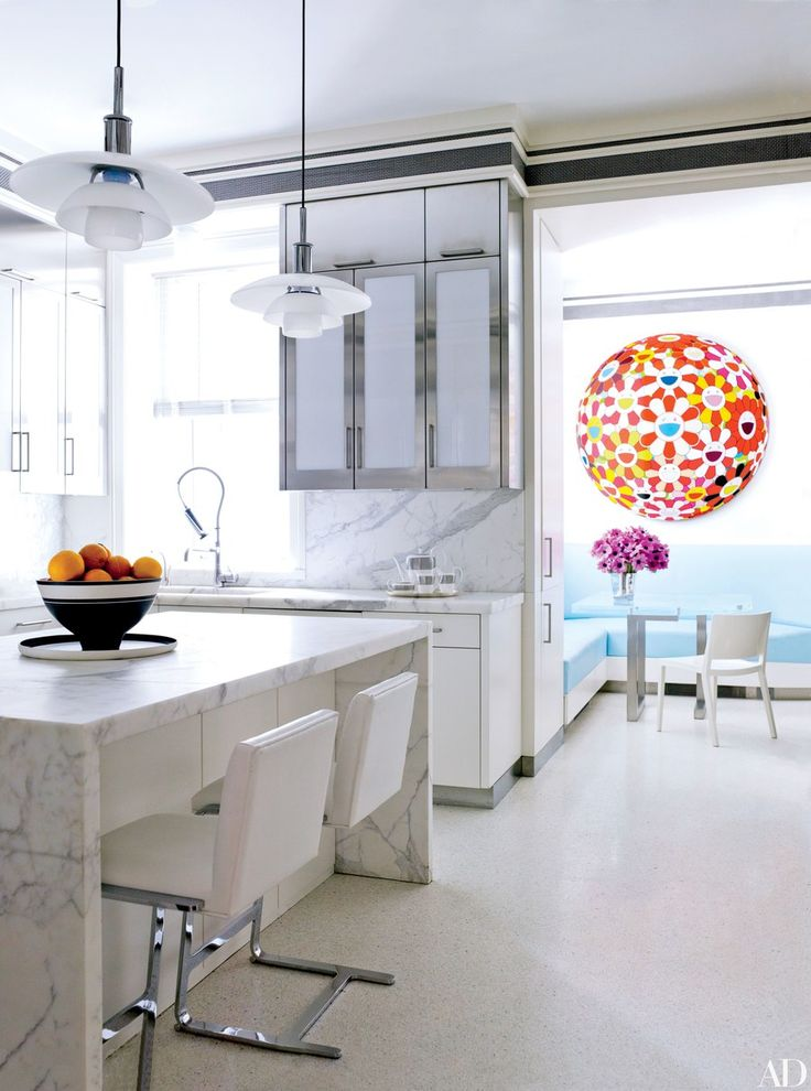 In a Manhattan home by David Kleinberg, a work by Takashi Murakami brightens the breakfast area of the kitchen, which has stainless-steel-and-milk-glass cabinetry and Calacatta gold marble counters and backsplashes.
