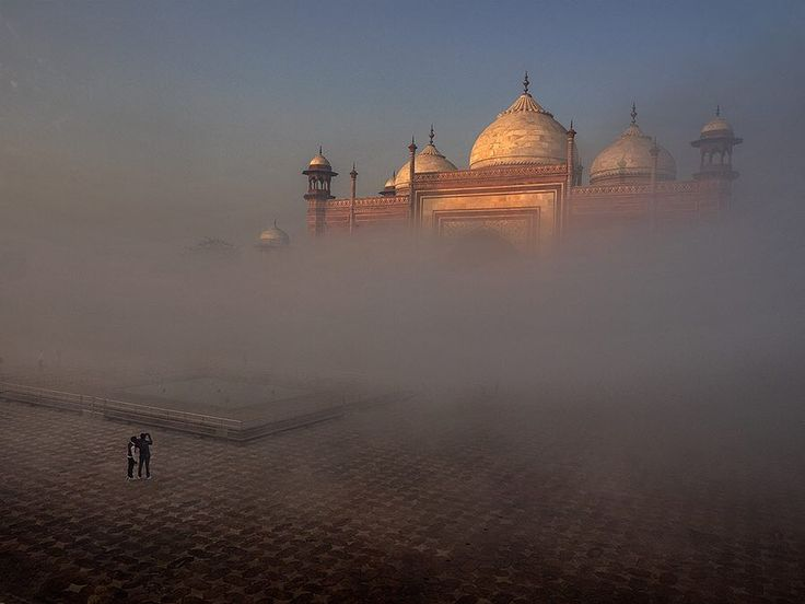 "@jaydickmanphoto  During the most recent National Geographic ""Around the World by Private Jet"" Expedition we had an ethereal morning at the Taj Mahal in Agra India. Fog lifting from the Yamuna River had occluded views of the Taj the fog started lifting as the morning progressed. Here a couple of visitors view one of the side mosques of the Taj Mahal as it is unveiled from the fog. Shot with Olympus E-M1 w/12-40mm Pro lens on Lexar media.  We still have a few spots available for the National…"