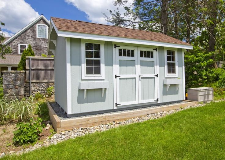 Modern garden shed painted grey with white highlights, twin windows, double barn doors and brown roof in beautiful garden
