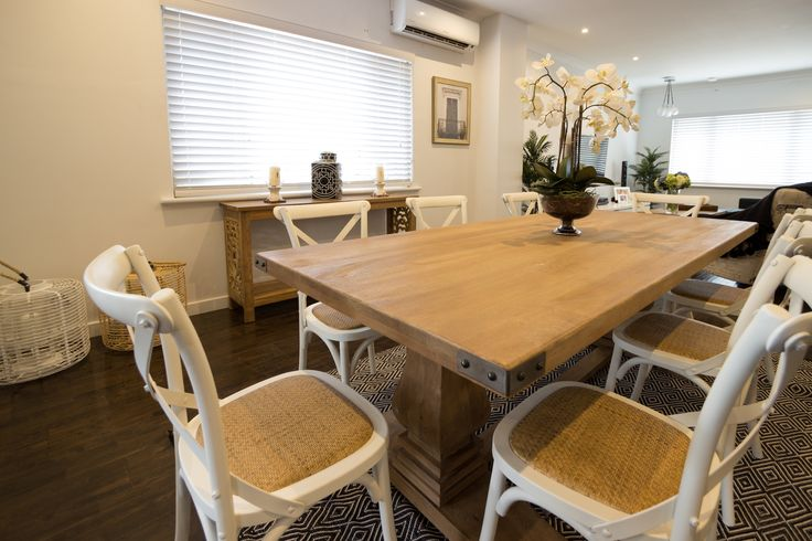 A casual dining room with a large timber table and white cross back chairs