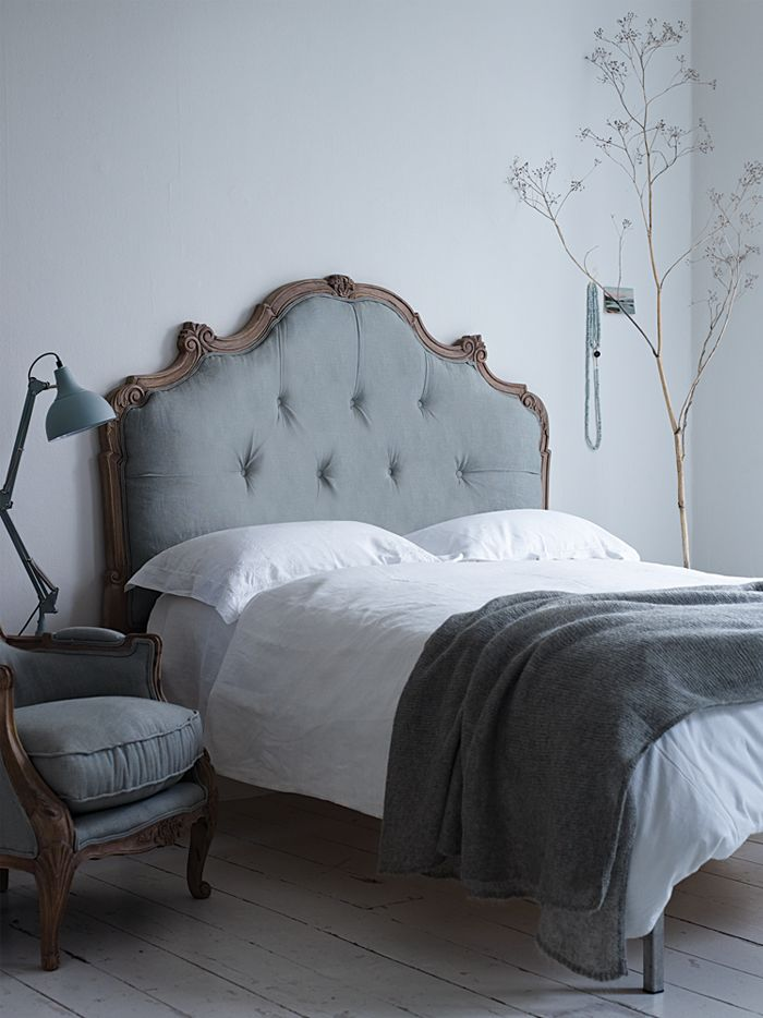Headboard of chocolate wood and blue tufted texture, with white sheets, charcoal throw and white-washed floors.