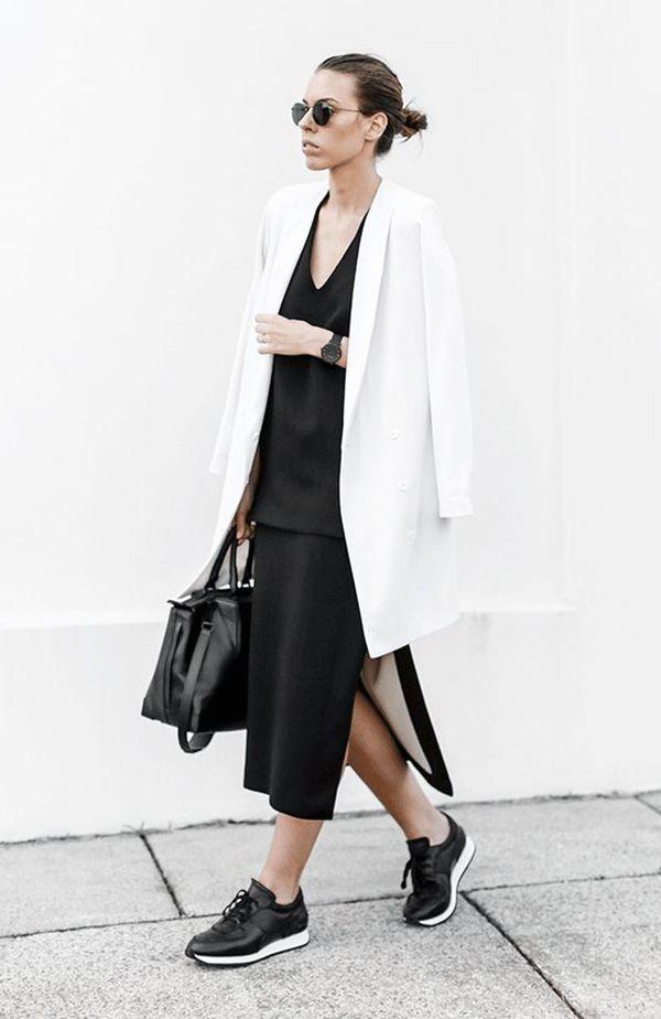 Kaitlyn Hamstyle com look de vestido preto e blazer branco oversizes, tênis de couro preto e bolsa preta