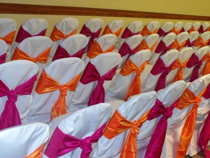 Alternating Orange and Fuschia Satin Cravats on White Chair Covers