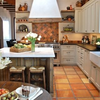 Warm & Earthy Mexican Kitchen. An antique brick backsplash, Saltillo floor tiles (made of terra cotta), and a viga ceiling (made of peeled tree trunk rafters) lend a cozy, earthy vibe to grey-painted cabinetry topped with soapstone counters.
