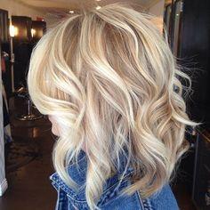 Dans ce beau carré mi-long et dégradé, le coiffeur de cette femme a réalisé des boucles légères et lâches. La coloration blonde, tout en nuances, rend l'ensemble très féminin.